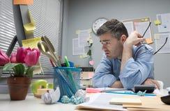 Deprimierter Büroangestellter an seinem Schreibtisch Lizenzfreies Stockbild