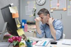 Deprimierter Büroangestellter an seinem Schreibtisch Stockbild