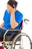 Deprimierter behinderter Mann, der auf einem Rollstuhl sitzt Stockfoto