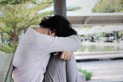 Deprimierter betonter junger asiatischer Geschäftsmann mit den Händen, die Kopf berühren und enttäuscht oder mit Job erschöpft gl Stockfoto