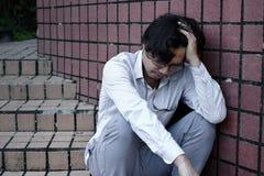 Deprimierter betonter junger asiatischer Geschäftsmann mit den Händen, die Kopf berühren und enttäuscht oder mit Job erschöpft gl Lizenzfreies Stockfoto