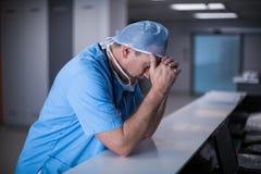 Deprimierter Chirurg, der auf Schreibtisch sich lehnt Stockbild