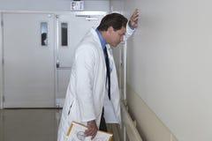 Deprimierter Doktor Leaning Against Wall Stockfotos