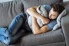 Deprimierter einsamer Mann, der auf dem Sofa liegt Lizenzfreies Stockfoto