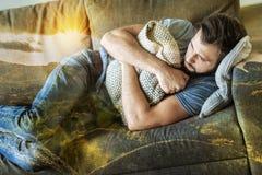 Deprimierter erschöpfter Mann, der beiseite schaut und das Kissen umarmt Lizenzfreie Stockfotografie