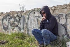 Deprimierter erwachsener Mann, der an gegen eine Steinwand mit einem Hoodie sitzt Lizenzfreie Stockbilder