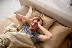 Deprimierter erwachsener Mann, der zu Hause unter einer Migräne leidet Lizenzfreie Stockfotos