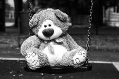 Deprimierter flaumiger weicher netter Teddy Bear Toy, der auf Wiege im Park sitzt lizenzfreies stockbild