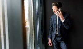 Deprimierter freudloser Geschäftsmann spricht auf Smartphone Lizenzfreies Stockbild