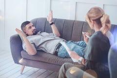 Deprimierter freudloser Mann, der auf dem Sofa liegt Stockfoto