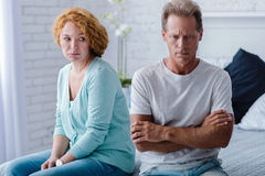 Deprimierter gealterter Ehemann und Frau, die auf dem Bett sitzt Lizenzfreies Stockfoto