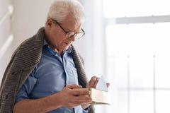 Deprimierter gealterter Mann, der alte Buchstaben in den Kasten einsetzt Lizenzfreies Stockfoto