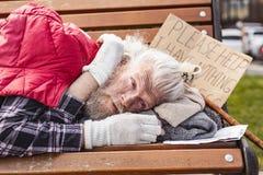 Deprimierter gealterter Mann, der auf der Bank liegt Stockfoto