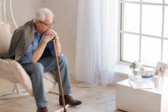 Deprimierter gealterter Mann, der im Lehnsessel sitzt Stockfoto