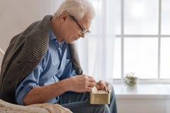 Deprimierter gealterter Mann, der nahe dem Fenster sitzt Lizenzfreie Stockfotos