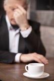 Deprimierter Geschäftsmann. Deprimierter reifer Geschäftsmann, der an t sitzt Stockbilder