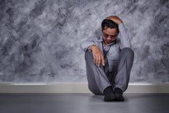 Deprimierter Geschäftsmann, der auf dem Boden sitzt Lizenzfreies Stockbild