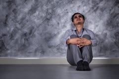 Deprimierter Geschäftsmann, der auf dem Boden sitzt Stockfotos