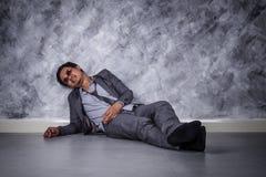 Deprimierter Geschäftsmann, der auf dem Boden sitzt Stockbild
