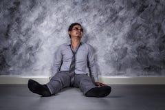 Deprimierter Geschäftsmann, der auf dem Boden sitzt Stockfotografie
