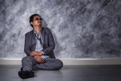 Deprimierter Geschäftsmann, der auf dem Boden sitzt Lizenzfreies Stockfoto