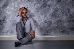 Deprimierter Geschäftsmann, der auf dem Boden sitzt Stockbilder