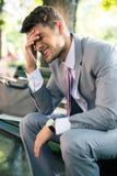 Deprimierter Geschäftsmann, der auf der Bank sitzt Stockbild