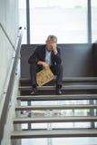 Deprimierter Geschäftsmann, der auf der Treppe hält Pappblatt mit Textbedarfsarbeit sitzt Lizenzfreies Stockbild
