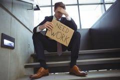 Deprimierter Geschäftsmann, der auf der Treppe hält Pappblatt mit Textbedarfsarbeit sitzt Lizenzfreie Stockbilder