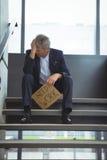 Deprimierter Geschäftsmann, der auf der Treppe hält Pappblatt mit Textbedarfsarbeit sitzt Lizenzfreies Stockfoto