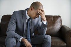 Deprimierter Geschäftsmann, der auf einer Couch sitzt Stockfotografie