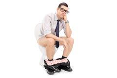 Deprimierter Geschäftsmann, der auf einer Toilette sitzt Lizenzfreies Stockfoto