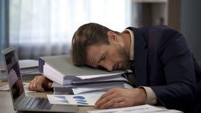 Deprimierter Geschäftsmann, der auf Stapel von Ordnern, Termindruck, Abführung liegt stockfoto