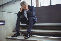 Deprimierter Geschäftsmann, der auf Treppe sitzt Stockfotos