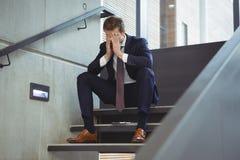 Deprimierter Geschäftsmann, der auf Treppe sitzt Lizenzfreies Stockfoto