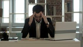 Deprimierter Geschäftsmann, der am Computer sitzt Stockfoto