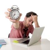 Deprimierter Geschäftsmann, der den Wecker sitzt am Schreibtisch arbeitet mit Computerlaptop im Fristenprojektkonzept hält Lizenzfreies Stockbild