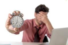 Deprimierter Geschäftsmann, der den Wecker sitzt am Schreibtisch arbeitet mit Computerlaptop im Fristenprojektkonzept hält Stockfotografie