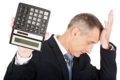 Deprimierter Geschäftsmann, der einen Taschenrechner hält Stockfotos