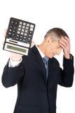 Deprimierter Geschäftsmann, der einen Taschenrechner hält Lizenzfreies Stockbild