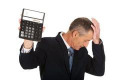 Deprimierter Geschäftsmann, der einen Taschenrechner hält Stockbilder