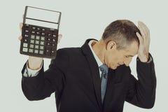 Deprimierter Geschäftsmann, der einen Taschenrechner hält Stockfoto