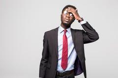 Deprimierter Geschäftsmann, der Kopfschmerzen auf grauem Hintergrund hat Stockfotografie