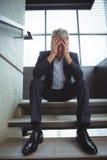 Deprimierter Geschäftsmann, der mit der Hand auf Kopf sitzt Lizenzfreie Stockfotos