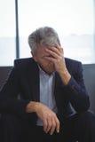 Deprimierter Geschäftsmann, der mit der Hand auf Kopf sitzt Stockfotos