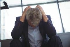 Deprimierter Geschäftsmann, der mit der Hand auf Kopf sitzt Lizenzfreies Stockbild