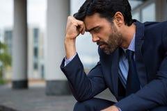 Deprimierter Geschäftsmann, der mit der Hand auf Stirn sitzt Stockbild