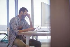 Deprimierter Geschäftsmann, der am Schreibtisch sitzt Stockfoto