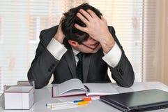 Deprimierter Geschäftsmann, der seinen Kopf im Büro hält Stockfoto