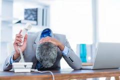 Deprimierter Geschäftsmann, der Telefon hält Lizenzfreie Stockfotografie